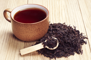 Black Tea in cup with dried leaves