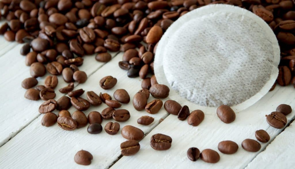 Coffee pods with coffee beans on the background