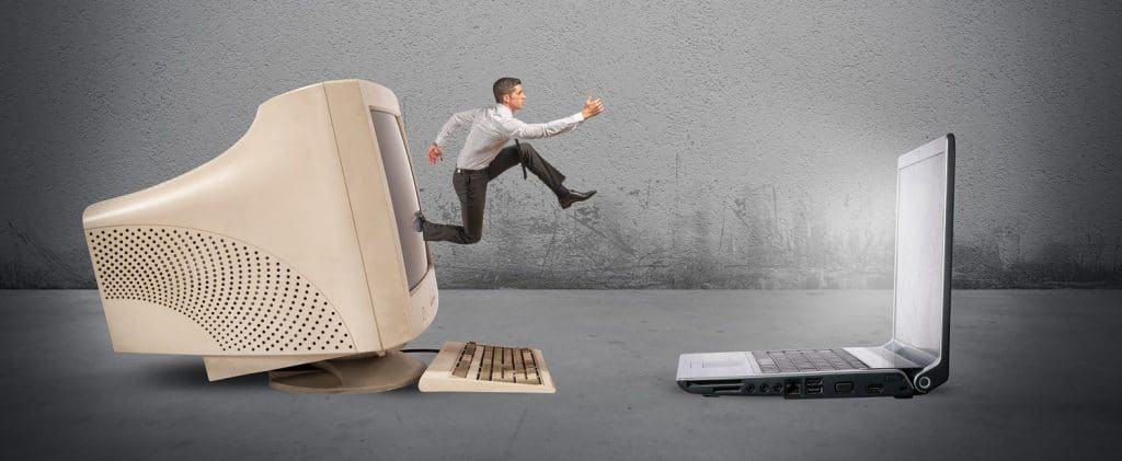 A man jumping from old desktop to new laptop