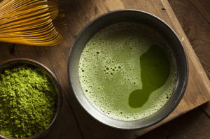 Matcha in a cup with matcha powder and whisk